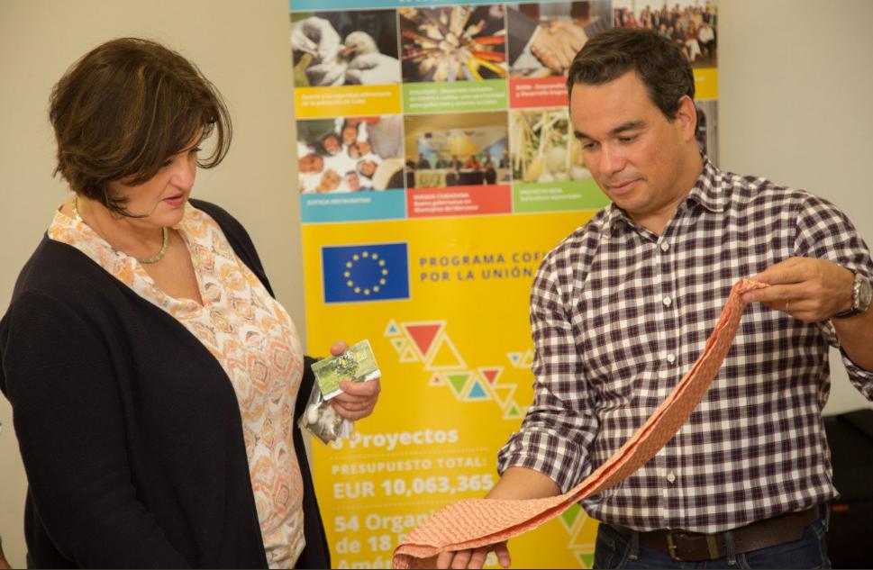Jolita Butkeviciene y Luis Pedro Pereira Mateus apreciando productos en seda realizados por pequeños productores de América Latina