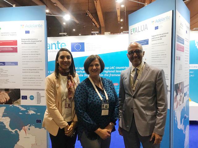 Laura Cabral e Hicham Boughdadi del equipo de Asistencia Técnica de ADELANTE acogiendo a Jolita Butkevicienne, Directora para América Latina y el Caribe de DG-DEVCO (Unión Europea) durante su visita a la exposición.